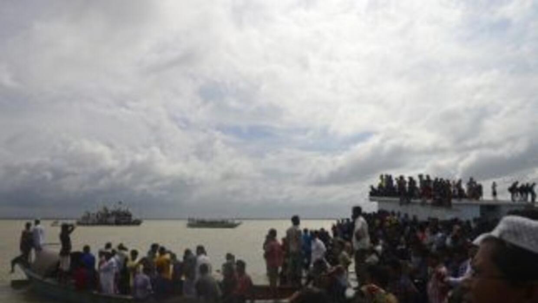 Decenas de curiosos se reúnen cerca del lugar donde se hundió el ferry e...