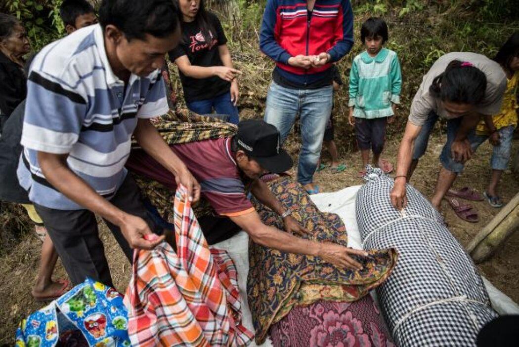 Familiares cubren un cuerpo sin vida durante el ritual de Manene en Indo...