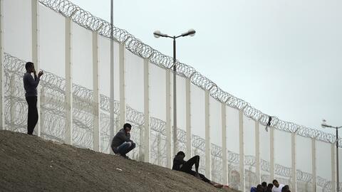 Migrantes de La Jungla, junto a la valla que protege la autopista de Cal...