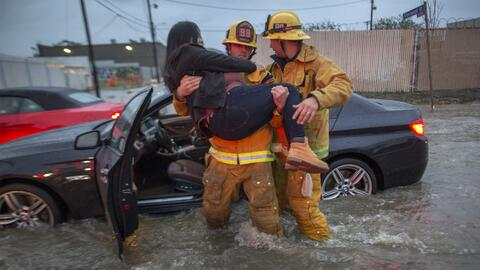 Un bombero carga a una mujer cuyo auto terminó atrapado en una co...