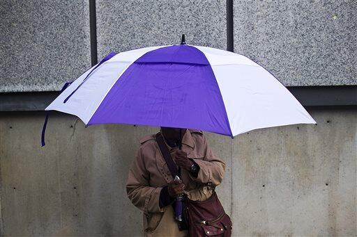 Una mujer se tapa de la lluvia con  una sombrilla mientras espera su aut...