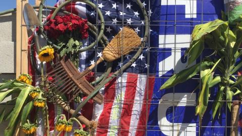 Elementos agrícolas, una bandera y un cartel de Trump en muro ant...