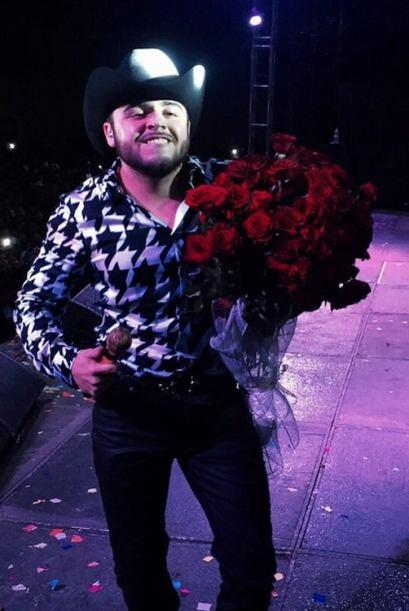Con este enorme ramo de rosas sale el cantante a cantar.