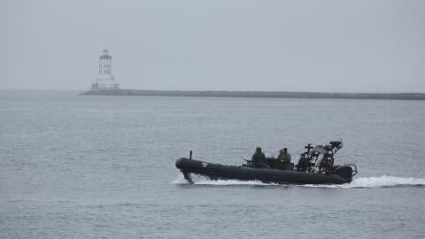 Una embarcación de rescate busca el helicóptero sumergido...