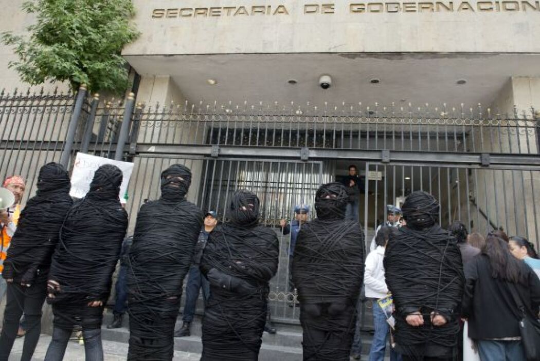 En la protesta varios activistas se envolvieron con hilo negro de pies a...