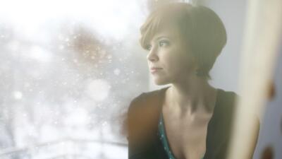 Mujer pensativa sentada en ventana