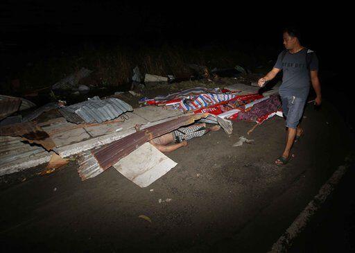 Residentes de laciudad de , al centro de Filipinas, caminan entre los e...
