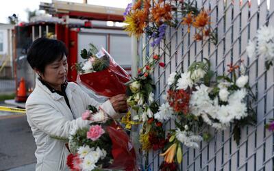 Una mujer pone flores en homenaje de las víctimas del incendio en...
