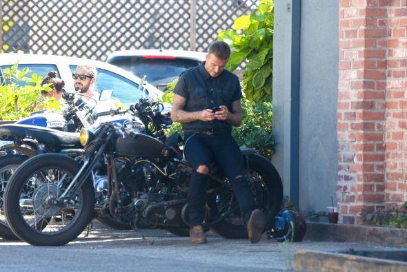Estuvo recargado contra una moto revisando sus mensajes.