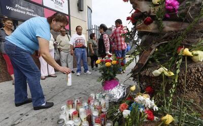 Una mujer deposita una vela en el altar calljero por las víctimas.