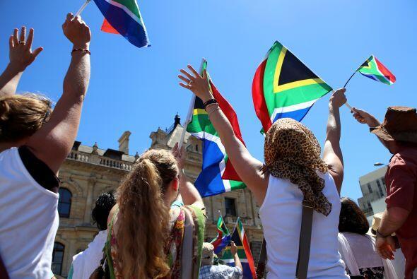 Sudafricanos animan y ondean banderas durante el discurso del presidente...