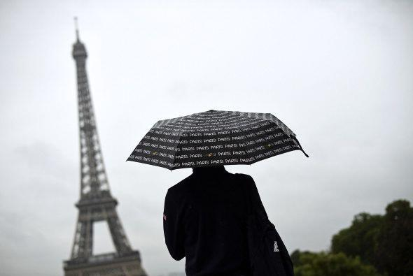 Un turista mira hacia la Torre Eiffel cubriéndose con un paraguas...
