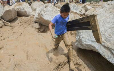 Un niño camina entre el lodo recogiendo escombros en la zona de M...