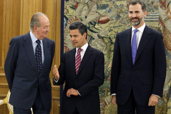 El rey Juan Carlos junto al príncipe Felipe conversan con el presidente...