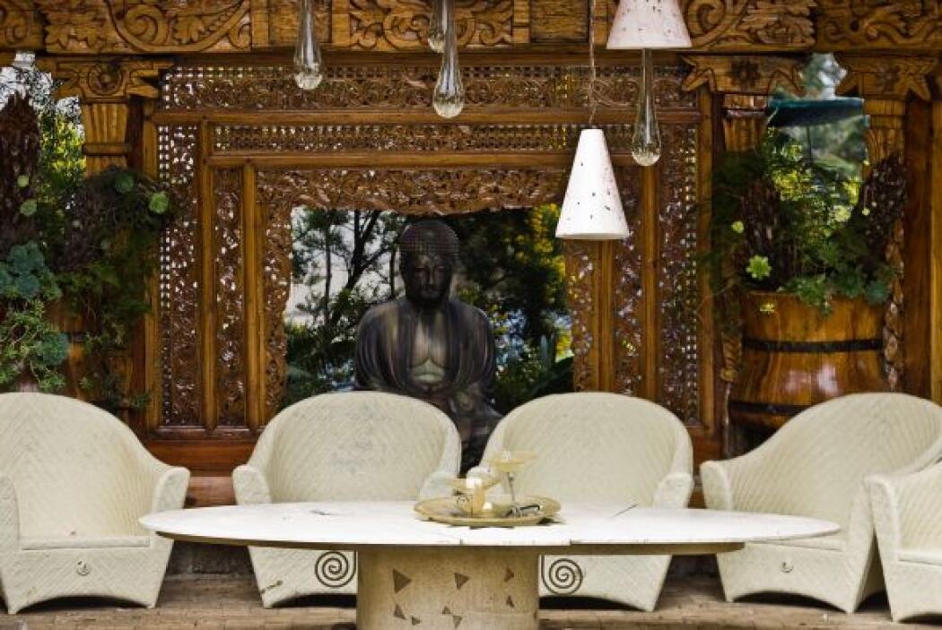 En este solar hay una figura budista, rodeada de sillas de tela blanca y...