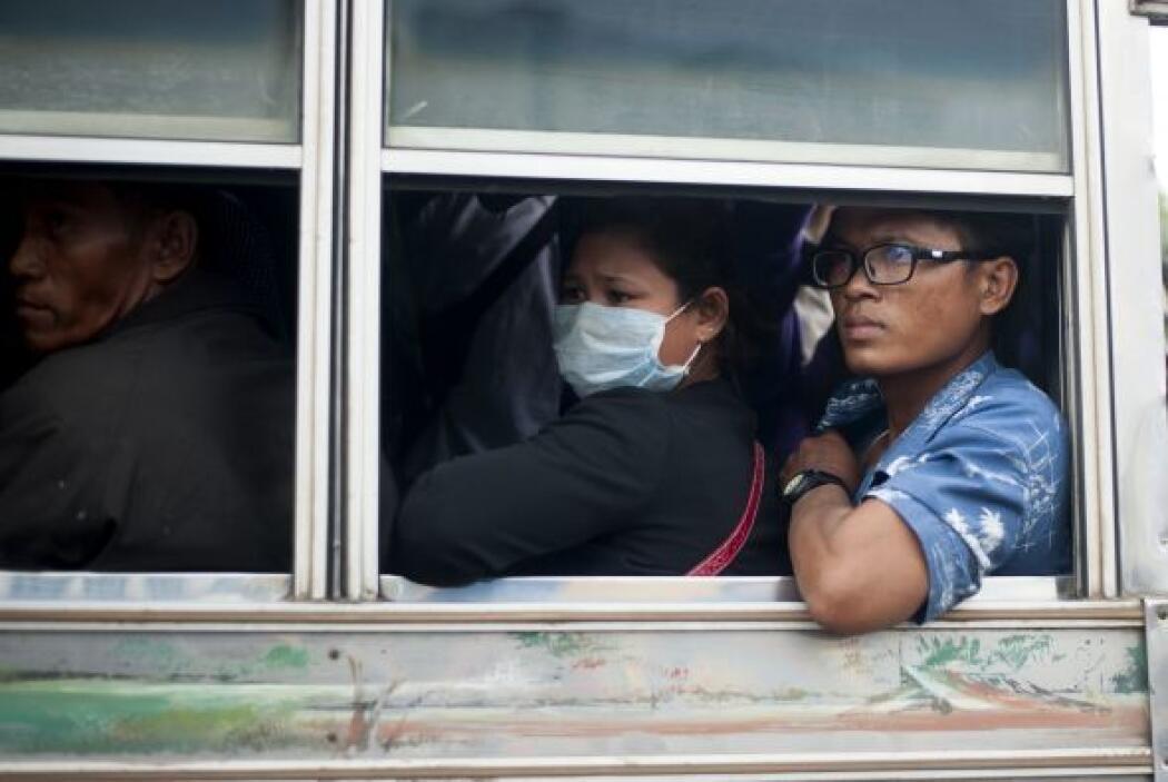 Trabajadores camboyanos miran por la ventana del autobús después de cruz...