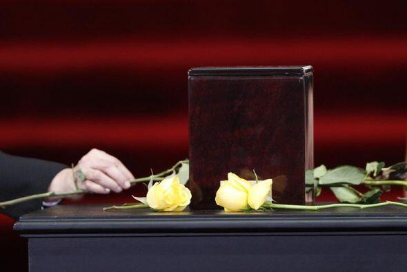 Al lado e la urna, dos grandes rosas amarillas lo acompañan.