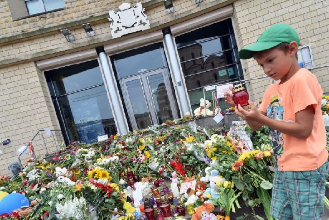 Un niño deposita una vela junto a los arreglos florales.