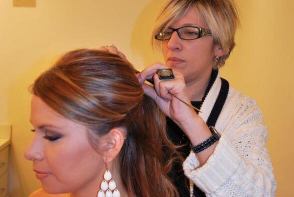 Después de maquillarla, la estilista le arreglo su cabello.