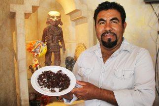 Un hombre muestra un plato de chapulines en el restaurante El Rincón Oax...