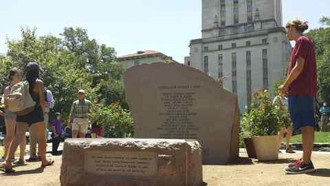 Varias personas contemplan el monumento a las 16 víctimas de la m...