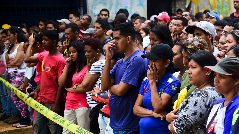 Vecinos observan cómo la policía retira los cuerpos de los fallecidos en...