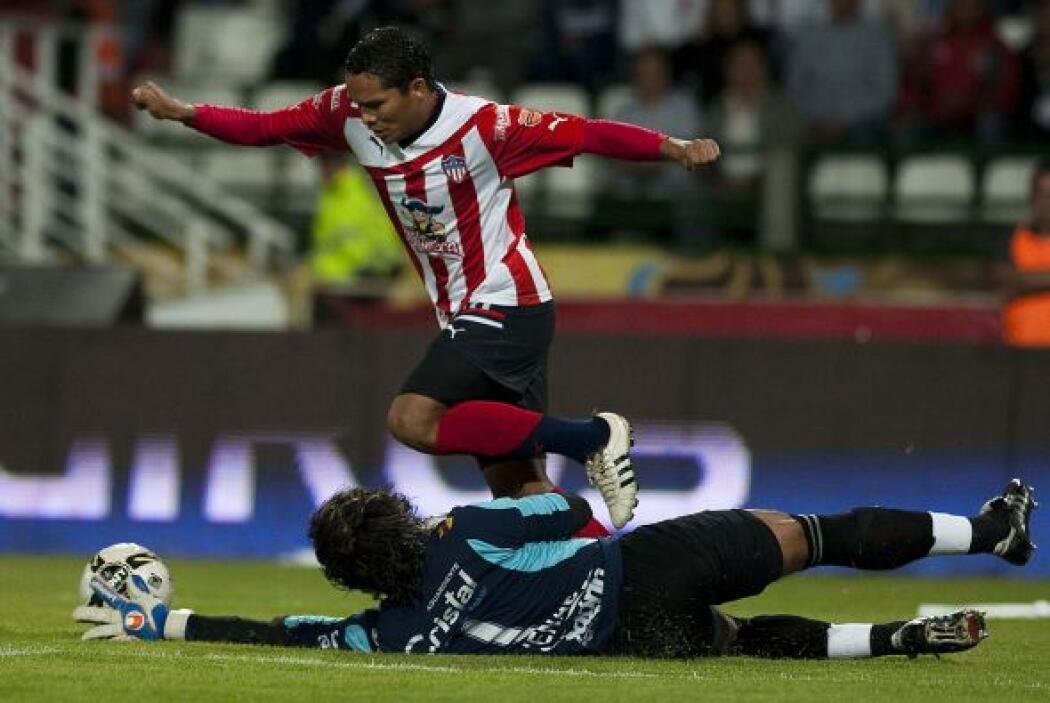 El portero Juan Carlos Henao, del Caldas intenta frenar el avance del go...