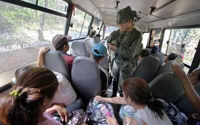 Soldados venezolanos inspeccionan a los pasajeros de un autobús.