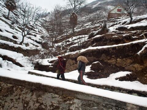 Un residente lleva un saco de arroz en la espalda mientras se dirige a c...