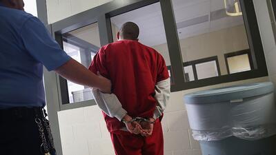 Un guardia escolta a un inmigrante indocumentado en el centro de detenci...