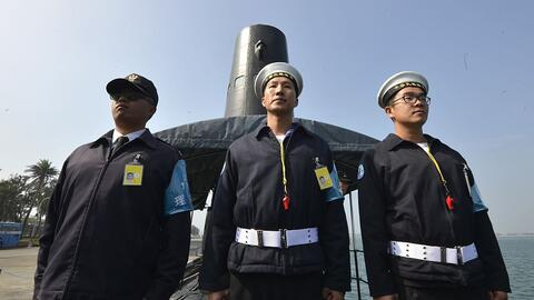 Marineros taiwaneses frente a un submarino en la base naval de Tsoying e...