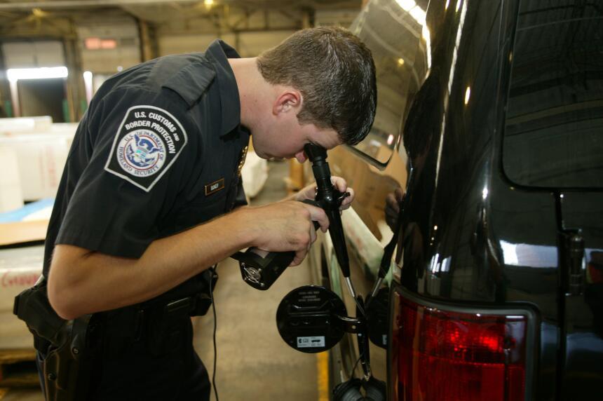 Un agente de Aduanas y Protección Fronteriza revisa el tanque de gasolina.