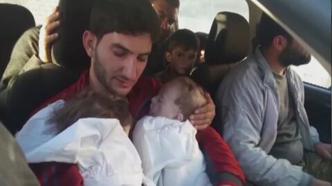 Un padre carga en brazos los cuerpos de sus dos hijas gemelas, fallecida...