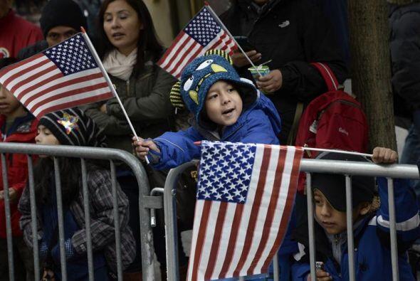 Niños ondean banderas de Estados Unidos durante el desfile del Día de lo...