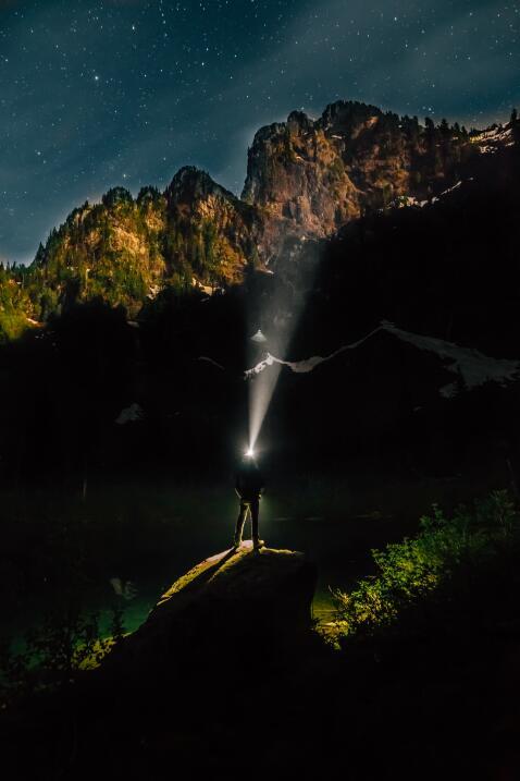 Un hombre con lámpara de cabeza posado sobre una roca mirando a las mont...