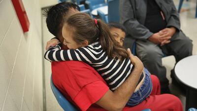 Un hombre detenido recibe la visita de sus hijos en Adelanto, California.