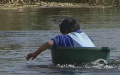 Unos  niños tienen que remar en improvisadas embarcaciones para ir a la...