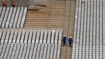 Trabajadores instalan los asientos en las graderías del estadio de Corin...