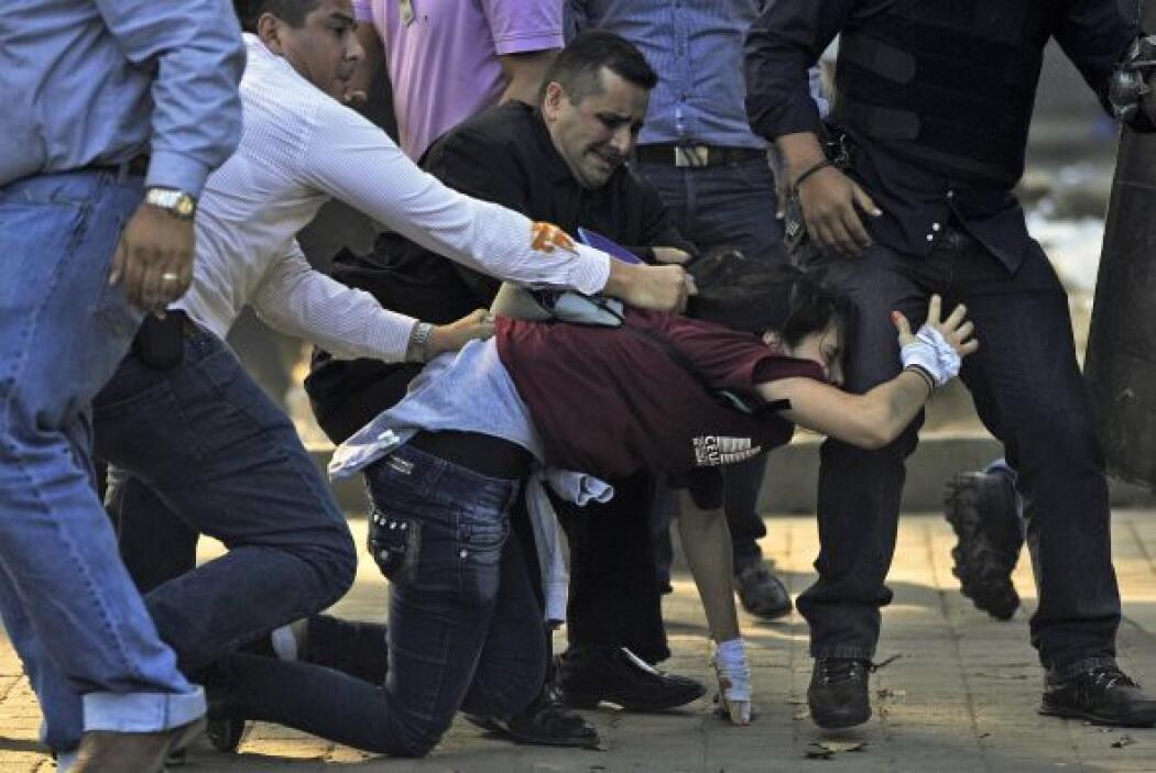 Agentes policíacos detienen a una joven manifestante.
