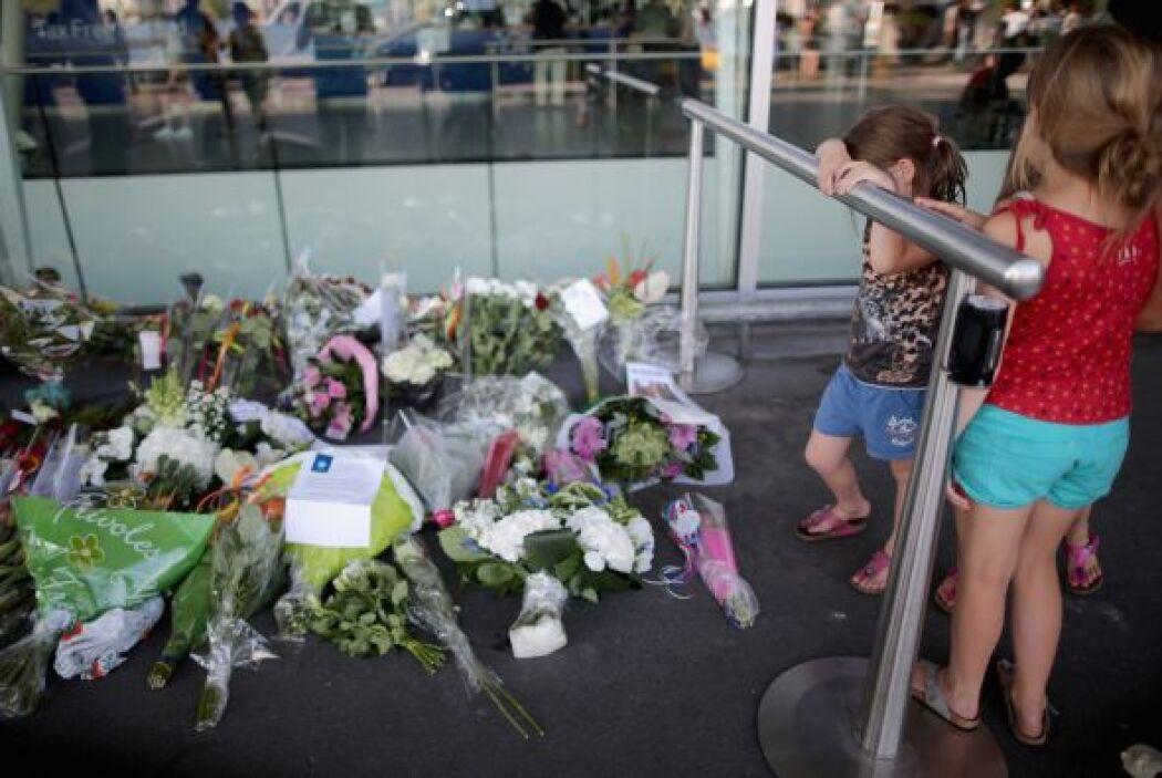 Un par de niñas admira la ofrenda floral que adorna la entrada al aeropu...