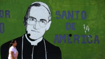 Una mujer pasa delante de un mural con la figura del arzobispo Oscar Rom...