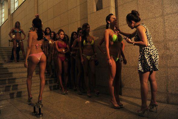 Fisicoculturistas mujeres se preparan antes de salir al escenario durant...