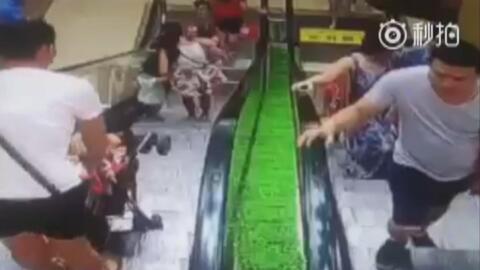 A este hombre se le cae el coche de su pequeño en una escalera mecánica