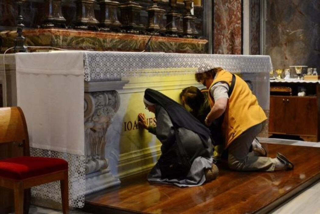 Peregrinos rezan ante la tumba del papa Juan Pablo II en la capilla de S...