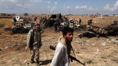 Fuerzas rebeldes en las afueras de Bengazi, pasan cerca de los restos de...