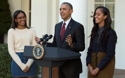 Barack Obama acompañado de sus hijas.