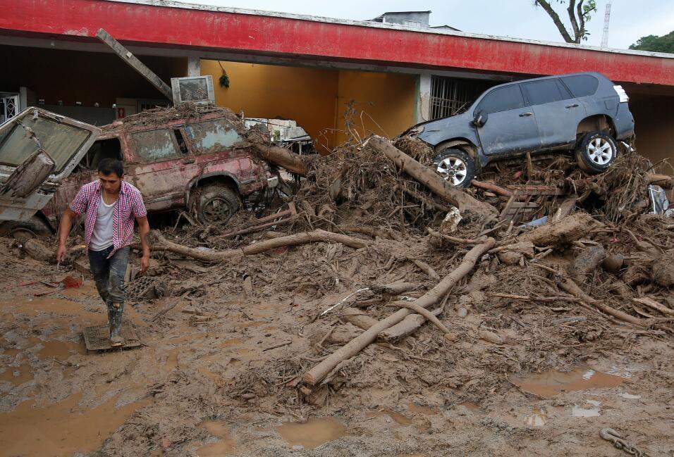 Un hombre camina por los escombros causados por las inundaciones y desla...