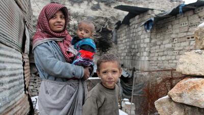 La nieve cubre el suelo cuando una familia de refugiados sirios está de...