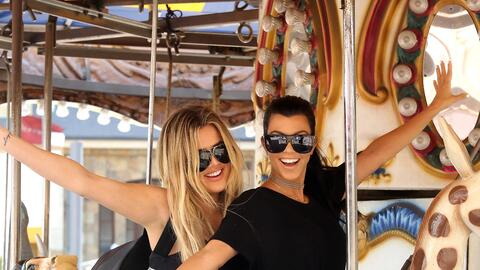 Kourtney y Khloé juegan sobre un carrusel.