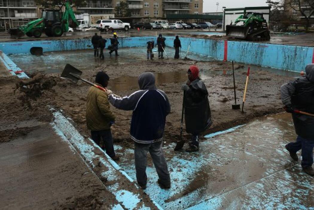 En esta imagen, trabajadores limpian una alberca que se econtraba cubier...